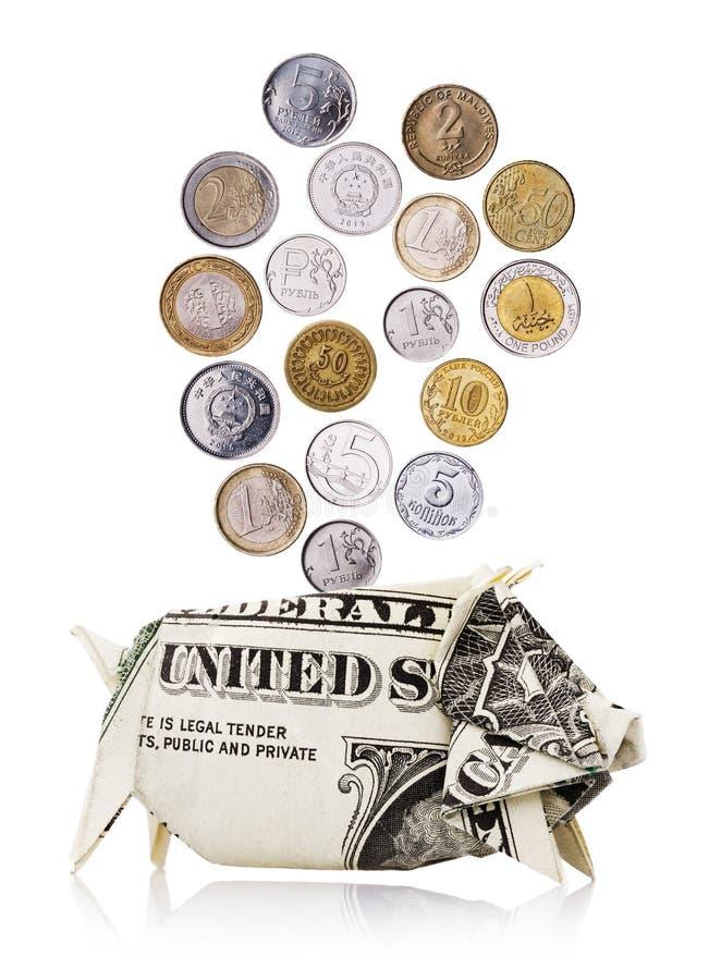 Münzen von verschiedenen Ländern fallen in ein Sparschwein lizenzfreie stockbilder