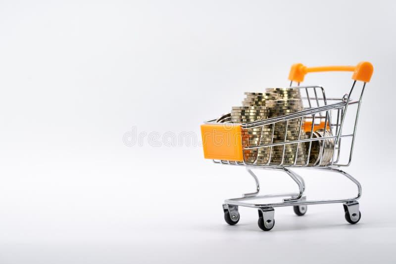 Münzenstapel im Einkaufswagen auf weißem Hintergrund stockbilder
