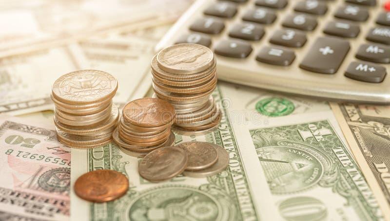 Münzenstapel mit Dollarscheinen und einem Taschenrechner lizenzfreies stockbild