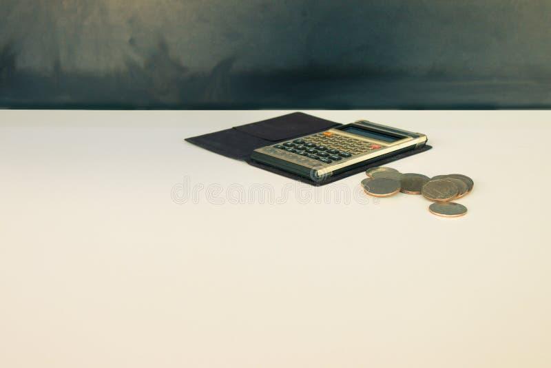 Münzgeld und Taschenrechner alt, Buch über weißem und schwarzem backgro lizenzfreies stockfoto