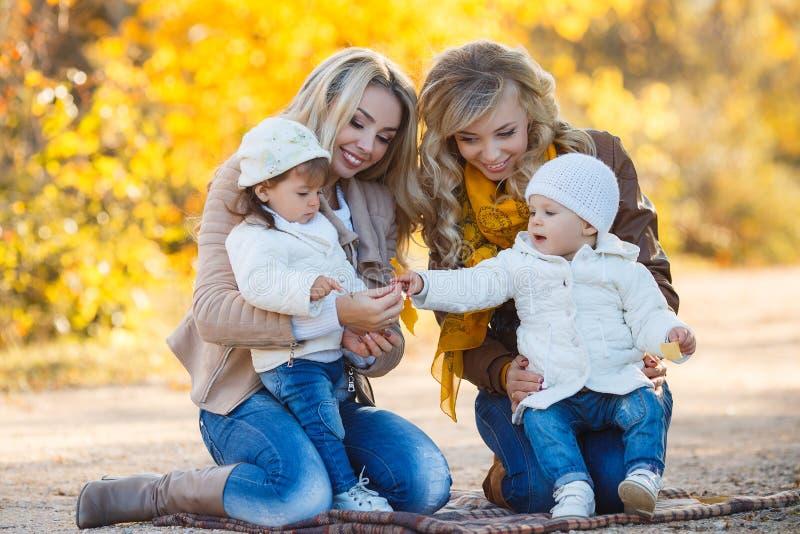 Mütter und Kinder für einen Weg im Park im Herbst lizenzfreie stockbilder