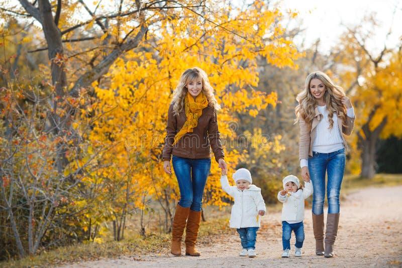 Mütter und Kinder für einen Weg im Park im Herbst lizenzfreie stockfotos