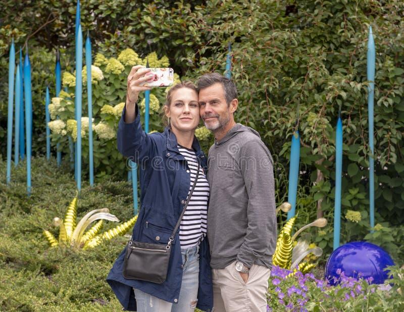 Mąż i żona bierzemy selfie zanim plenerowy eksponat w ogródzie, Chihuly ogród i szkło w Seattle, Ześrodkowywamy zdjęcia stock