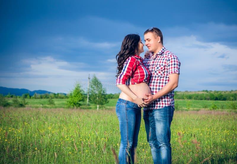 Mąż i jego ciężarna żona chodzimy przy sunse obrazy royalty free