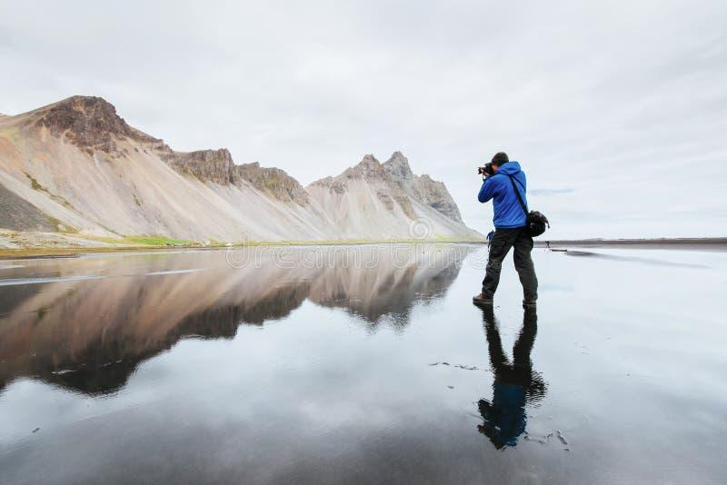 Mąż jest fotografa pozycją na wodnej powierzchni przy wybrzeżem Iceland w Stokksnes zdjęcia stock