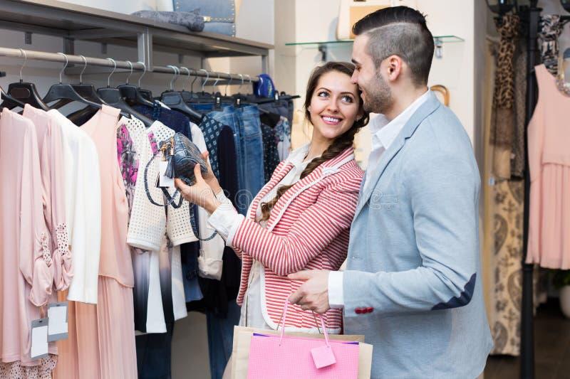 Mąż pomaga żona wybierać odzieżowego fotografia stock