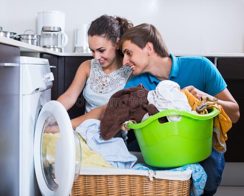 Mąż pomaga gospodyni domowa używać pralkę indoors zdjęcie stock