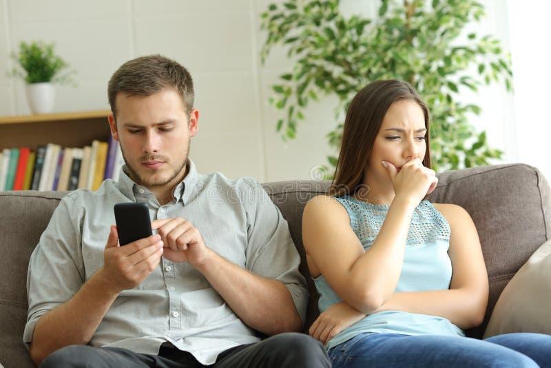 Mąż uzależniający się dzwonić i zmartwiona żona obrazy stock