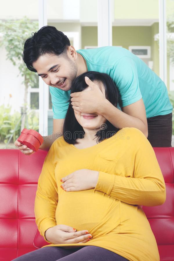 Mąż zaskakuje ciężarnej żony z prezentem obraz royalty free