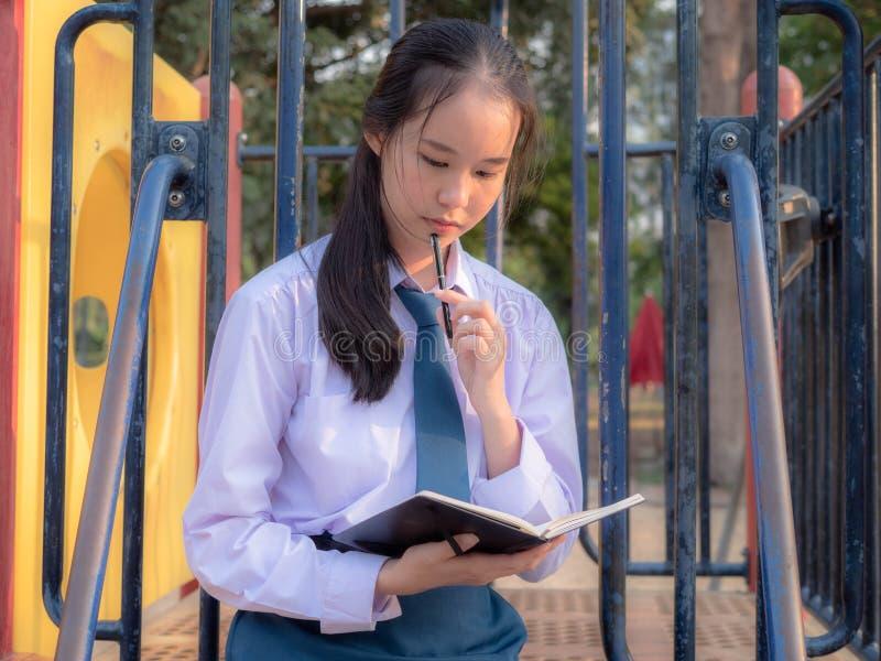 Mądra nastoletnia dziewczyna jest ubranym mundurek szkolnego pisze książce podczas gdy myśleć przy parkiem, pojęciem, natury, edu fotografia stock