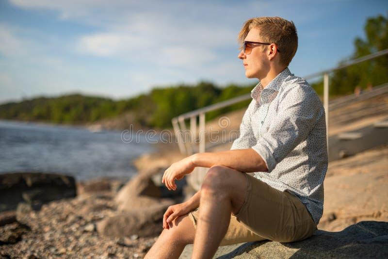Mądry Młody Człowiek Siedzi Na Skale Patrząc Na Morze zdjęcia stock