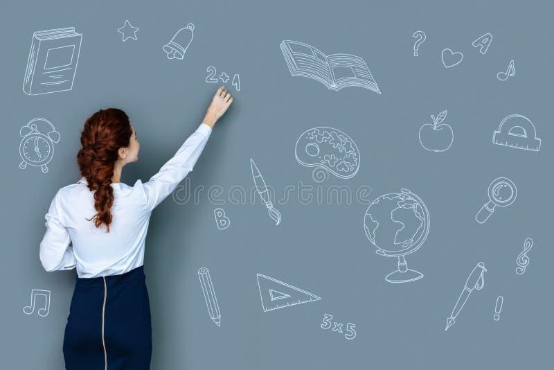 Mądry nauczyciel wyjaśnia nowego temat i pisze na blackboard obrazy royalty free