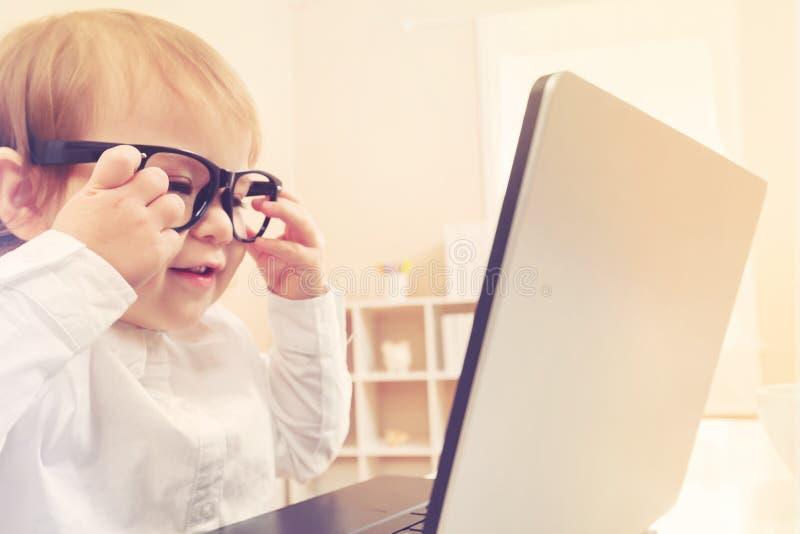 Mądrze berbeć dziewczyna jest ubranym dużych szkła używać jej laptop obrazy royalty free