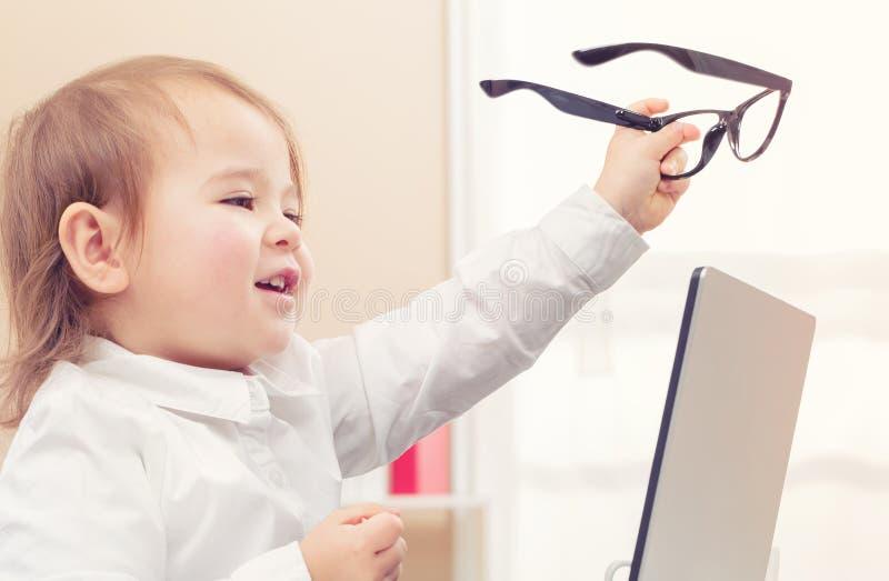 Mądrze berbeć dziewczyna jest ubranym dużych szkła używać jej laptop obrazy stock