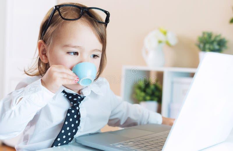 Mądrze berbeć dziewczyna pije kawę z szkłami podczas gdy używać laptop fotografia royalty free