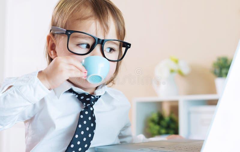 Mądrze berbeć dziewczyna pije kawę z szkłami podczas gdy używać laptop fotografia stock