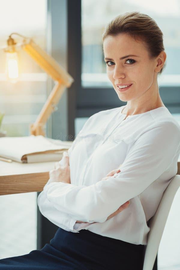 Mądrze bizneswomanu obsiadanie z jej rękami krzyżować podczas gdy być samotny fotografia royalty free