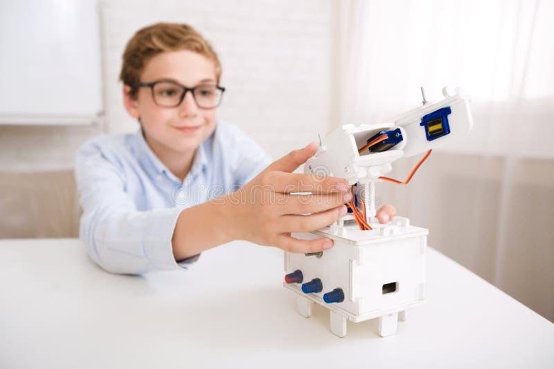 Mądrze chłopiec bada jego mechanicznego przyrząd na inżynierii klasach fotografia royalty free
