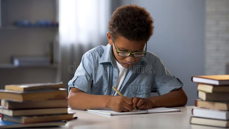 Mądrze chłopiec starannie pisze pracie domowej w jego notatniku, skrzętny uczeń obraz stock