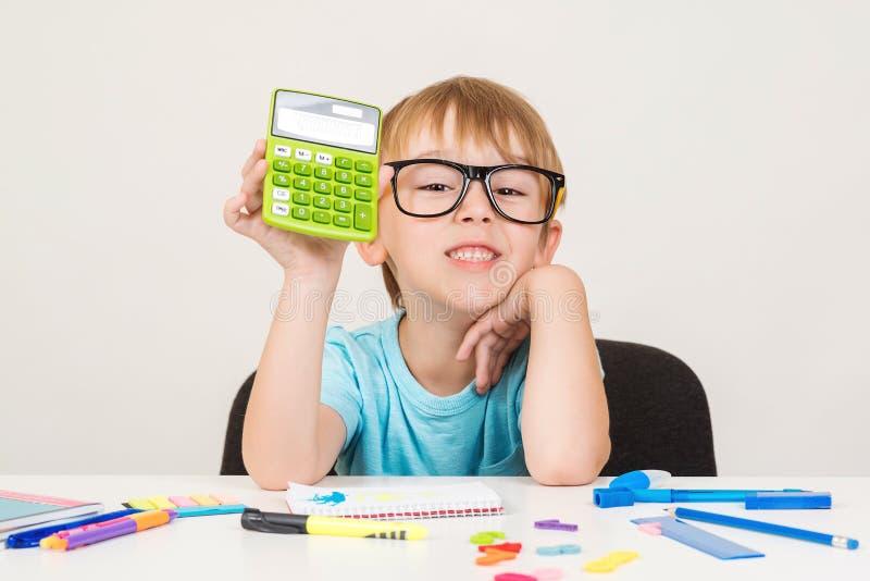 Mądrze chłopiec używa kalkulatora Dzieciak oblicza out matematyka problem w szkłach Rozwija logiczne umiejętności Szczęśliwa szko obraz stock