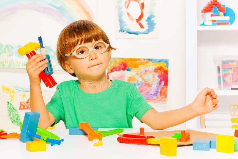 Mądrze chłopiec z klingerytów narzędziami w sala lekcyjnej zdjęcia royalty free