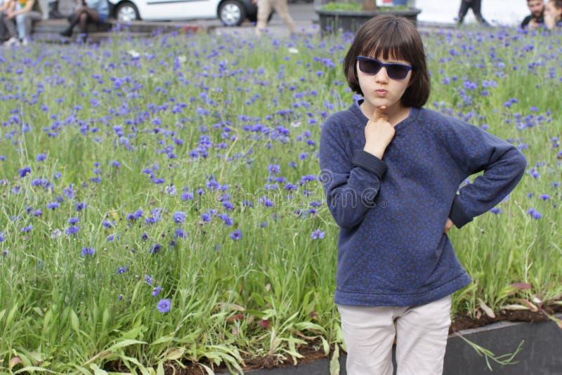 Mądrze dziecko wprawiać w zakłopotanie w mieście nad pokojowym chabrowym ogródem fotografia royalty free