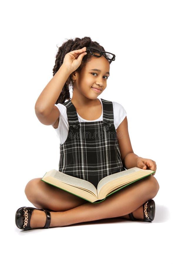 Mądrze dziewczyna czyta dużą zieleni książkę obraz stock
