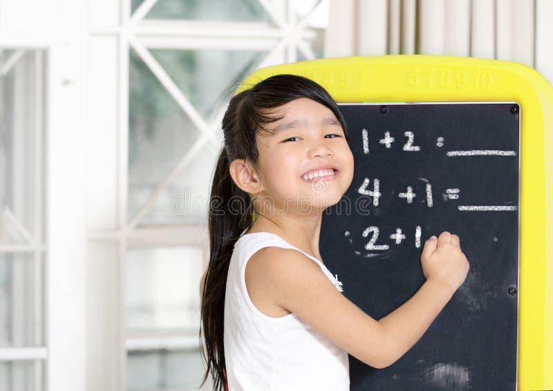 Mądrze mała dziewczynka ono uśmiecha się przed blackboard fotografia stock