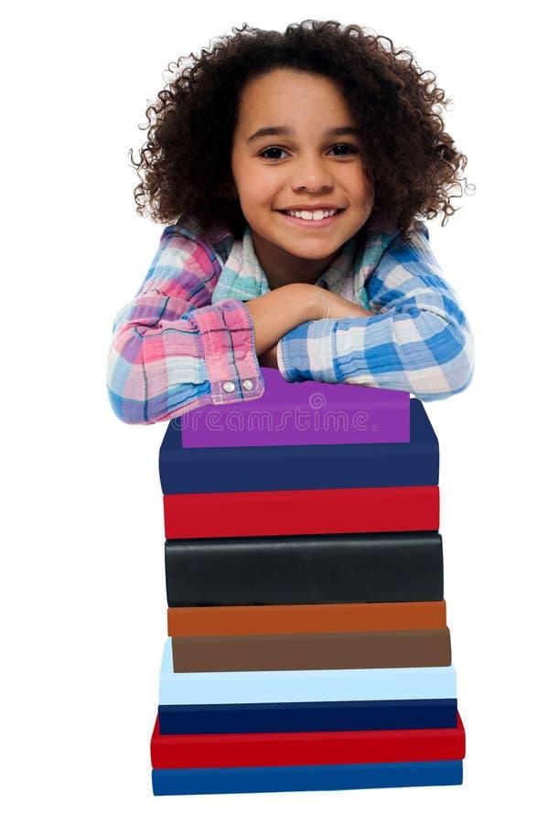 Mądrze mała dziewczynka opiera nad stosem książki obrazy stock