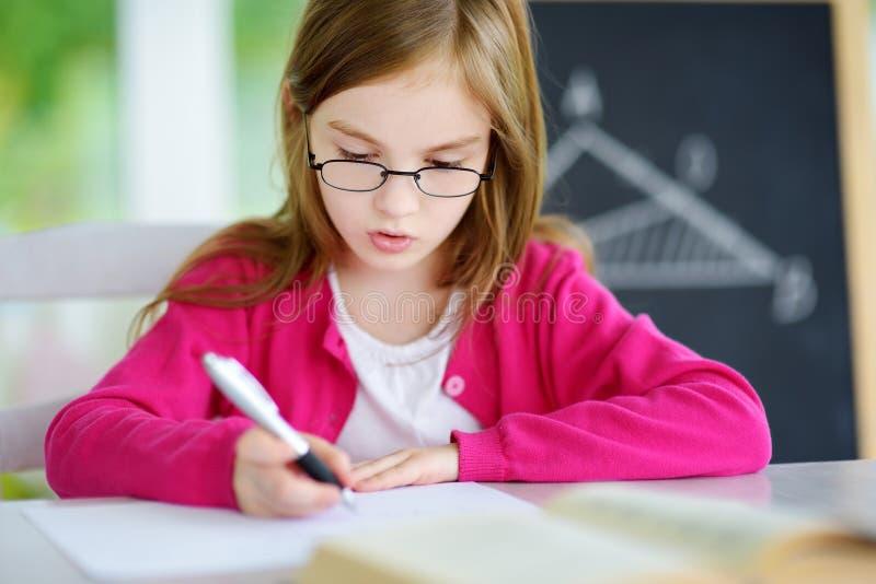 Mądrze mała uczennica pisze tescie w sala lekcyjnej z piórem i książki Dziecko w szkole podstawowej obraz royalty free