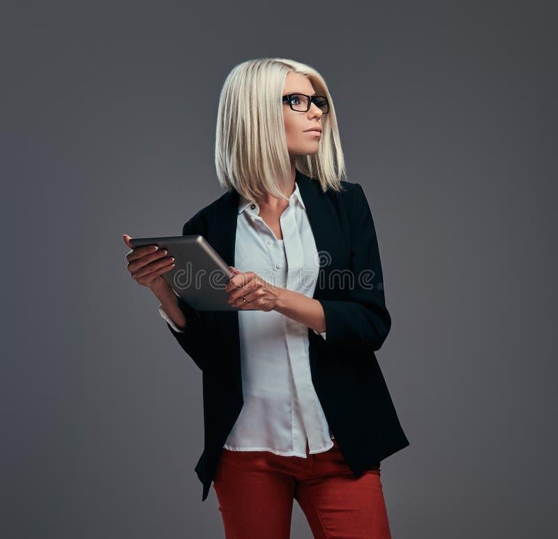 Mądrze modna blogger kobieta w nowożytny odzieżowym i szkła, pozy z cyfrową pastylką na szarym tle fotografia stock