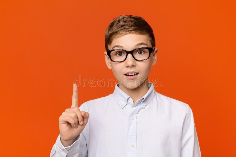 Mądrze nastoletnia chłopiec w szkłach ma pomysł zdjęcia stock