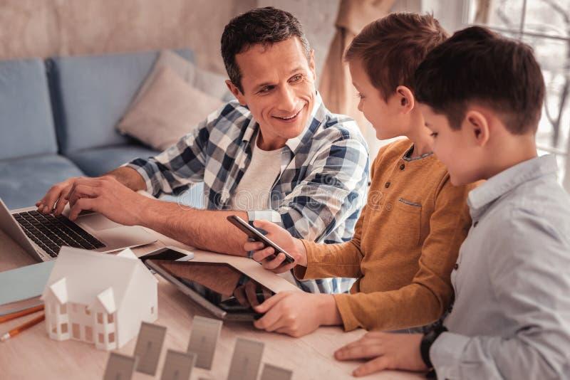 Mądrze oddany ojciec mówi jego synów o energii odnawialnej fotografia royalty free