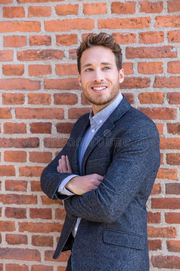 Mądrze przypadkowy biznesmen na miastowym miasto ściany z cegieł tła styl życia portrecie Młody fachowy mężczyzny ono uśmiecha si fotografia royalty free