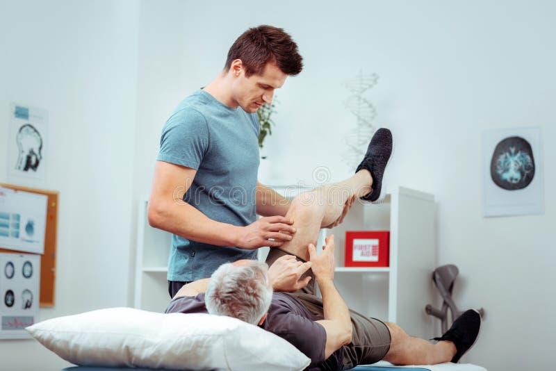M?drze przystojny m??czyzna sprawdza jego pacjent nog? fotografia stock