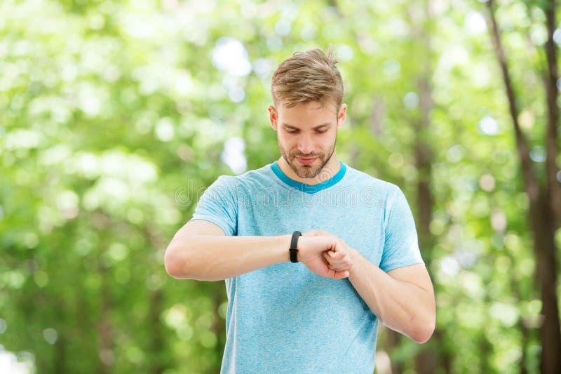Mądrze sprawność fizyczna Dysponowana atleta tropi jego sprawności fizycznej aktywność z sporta zegarkiem Przystojna atleta używa zdjęcie royalty free