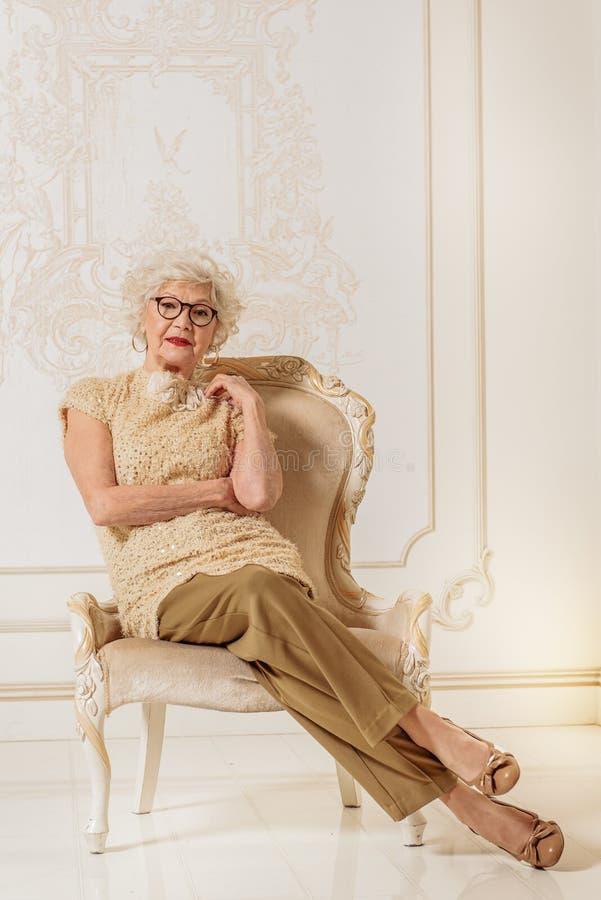 Mądrze stara kobieta relaksuje na luksusowym krześle zdjęcia stock