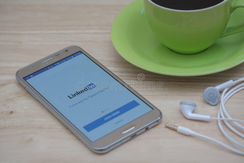 Mądrze telefon z ogólnospołecznym usługi sieciowe LinkedIn na ekranie z podróż materiałem na drewnianym biurku zdjęcie stock