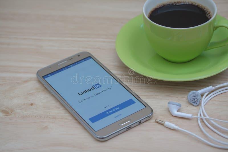 Mądrze telefon z ogólnospołecznym usługi sieciowe LinkedIn na ekranie z podróż materiałem na drewnianym biurku obrazy royalty free
