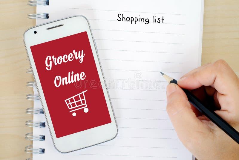 Mądrze telefon z sklepem spożywczym online na ekranie i lista zakupów plecy fotografia stock