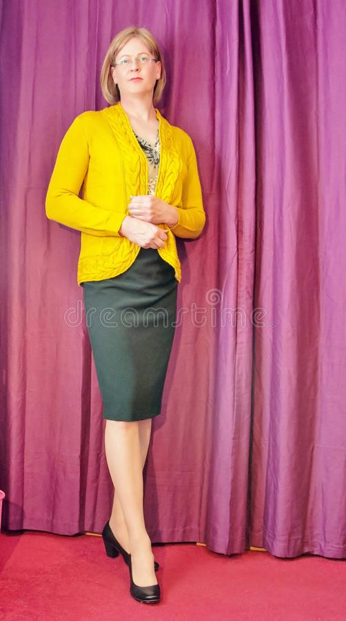 Mądrze ubierająca w średnim wieku kobieta jest ubranym żółtego kardigan czarną ołówek spódnicę i zdjęcia stock