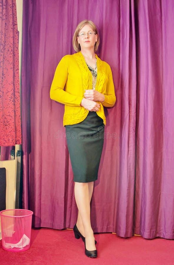 Mądrze ubierająca w średnim wieku kobieta jest ubranym żółtego kardigan czarną ołówek spódnicę i zdjęcie royalty free