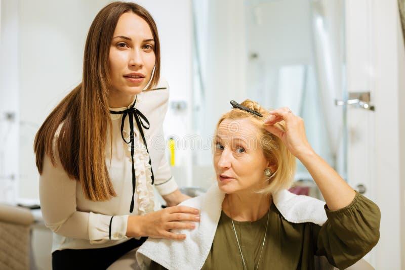 Mądrze wykwalifikowany fryzjer słucha jej klient obrazy royalty free