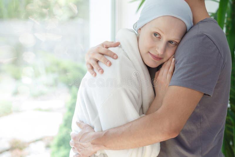 Męża przytulenia kobieta z nowotworem fotografia stock