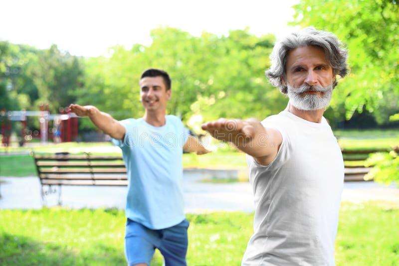 Mężczyźni ćwiczy ranku joga w pogodnym zdjęcia stock