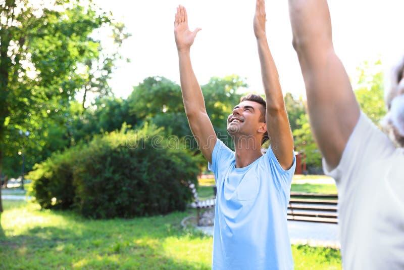 Mężczyźni ćwiczy ranku joga w pogodnym parku fotografia stock