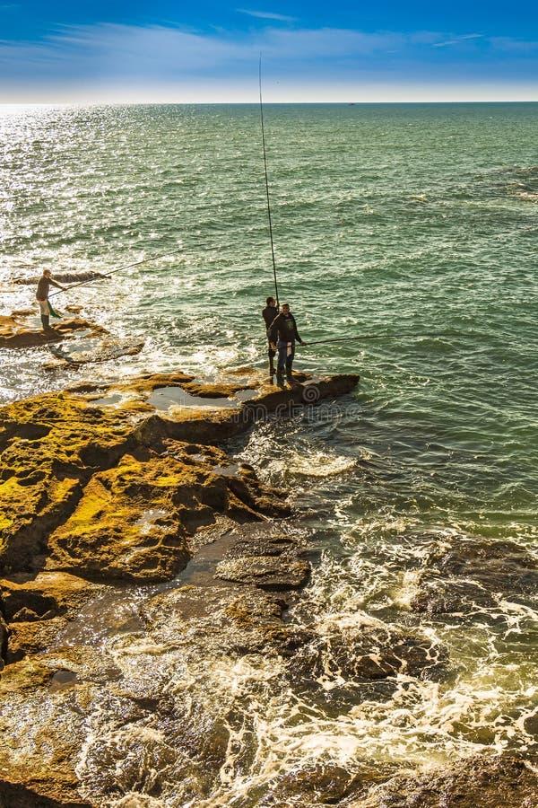 Mężczyźni łowi z skał Paseo Fernando chinony w Cadiz obrazy stock