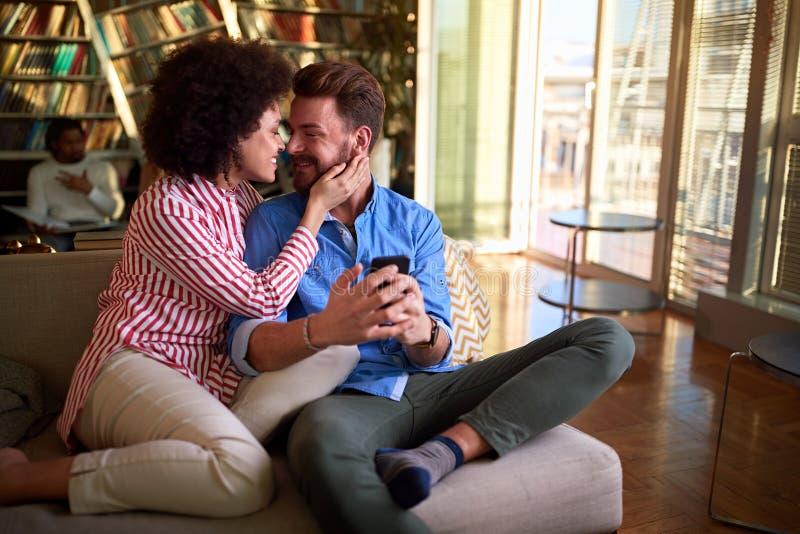 Mężczyźni i kobiety dzielą się knajpkami w salonie zdjęcia stock
