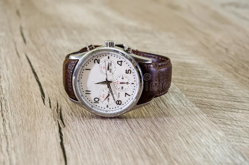Mężczyźni, wristwatches z brąz patką na drewnianym tle zdjęcie stock