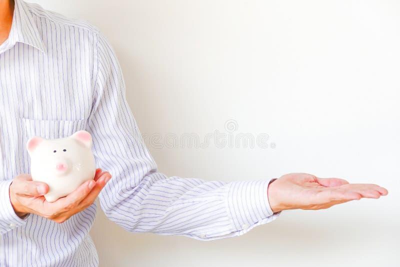 Mężczyźni z białą koszula pokazuje jego prawą stronę w kopii przestrzeni podczas gdy mieć prosiątko banka w rękach obrazy stock